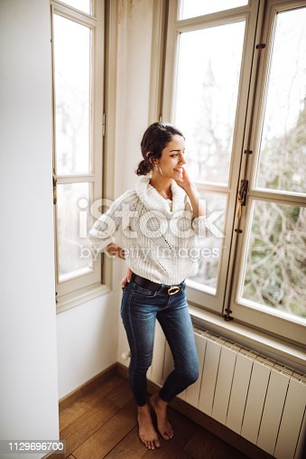 917874758 istock photo pensive woman in front of the window 1129696700