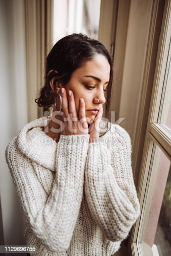 917874758 istock photo pensive woman in front of the window 1129696755