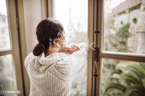 917874758 istock photo pensive woman in front of the window 1129696790