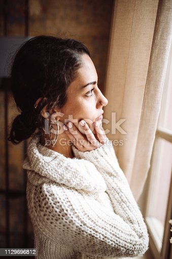 917874758 istock photo pensive woman in front of the window 1129696812
