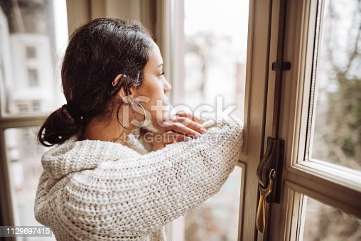 pensive woman in front of the window