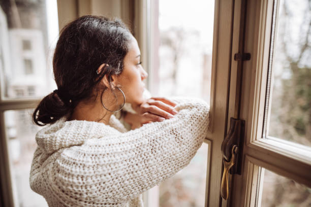 pensive woman in front of the window pensive woman in front of the window guilty stock pictures, royalty-free photos & images