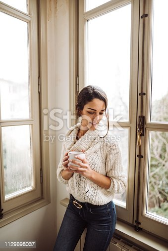 917874758 istock photo pensive woman in front of the window 1129698037