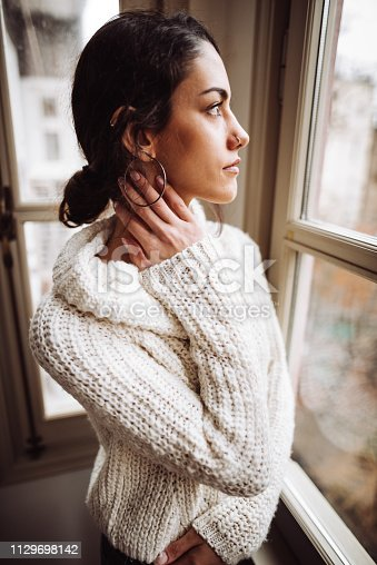 917874758 istock photo pensive woman in front of the window 1129698142