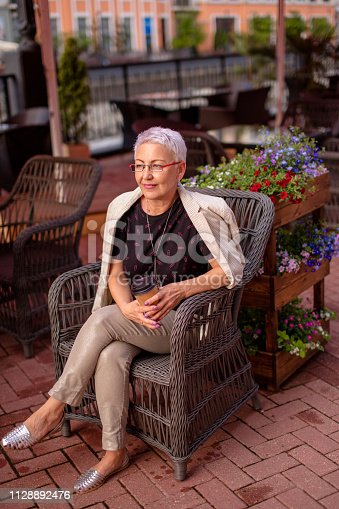 istock pensive woman is resting in the street restaurant 1128892476
