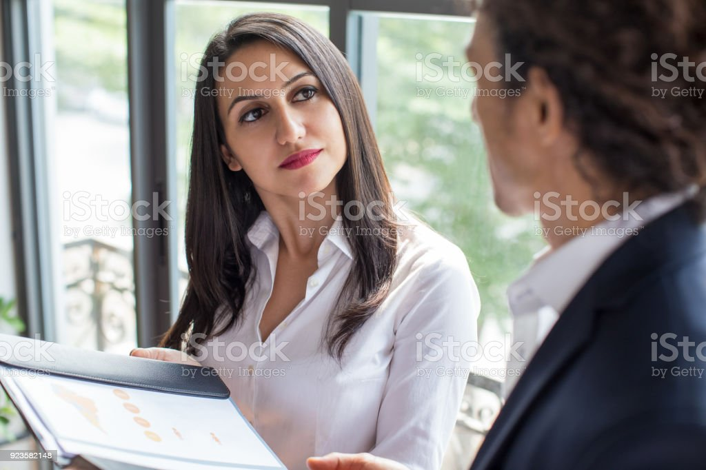 Pensive woman listening to coworker stock photo