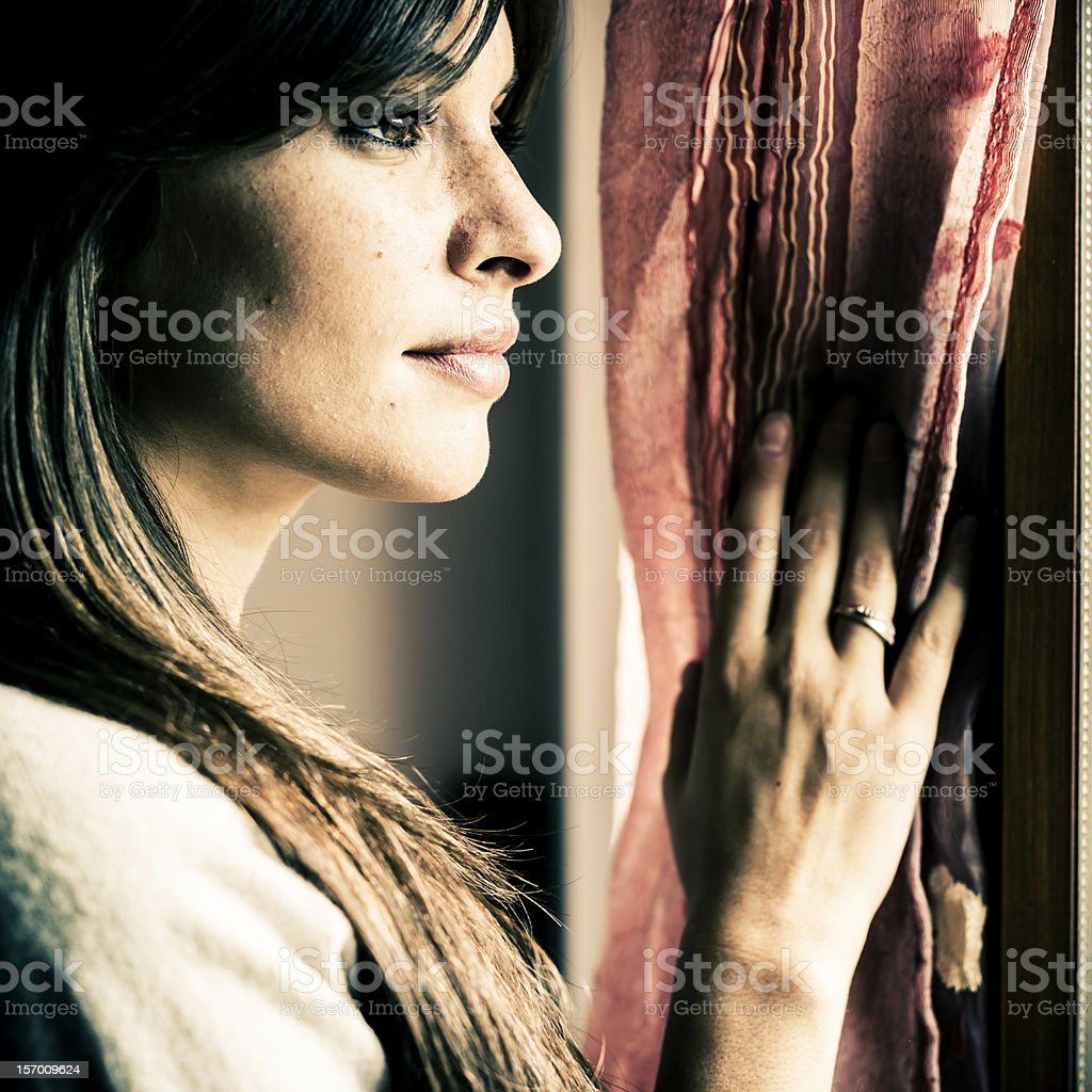 Pensive woman looking through a window royalty-free stock photo