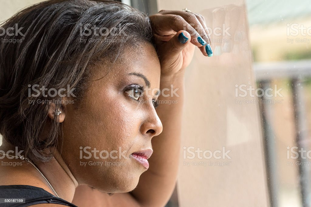 Pensive woman looking through the window stock photo