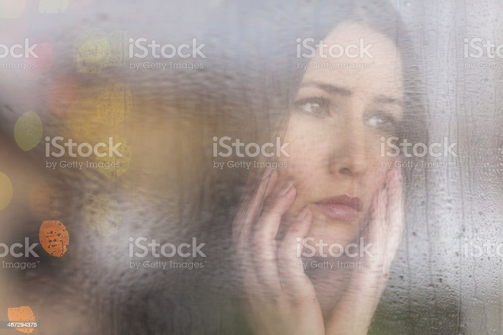 Beautiful young woman looking through the window on a rainy day