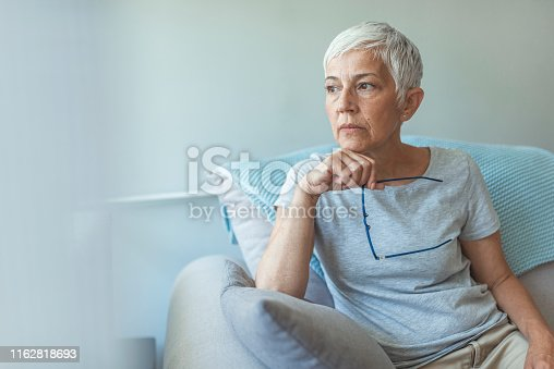 Feeling Down. Middle aged woman in glasses looking down. Portrait of pensive worried senior woman looking through the window and thinking. Pensive woman.