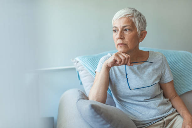 Pensive woman. Feeling Down. Middle aged woman in glasses looking down. Portrait of pensive worried senior woman looking through the window and thinking. Pensive woman. worried stock pictures, royalty-free photos & images