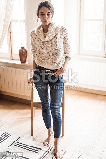 istock pensive woman posing at home 1130167559