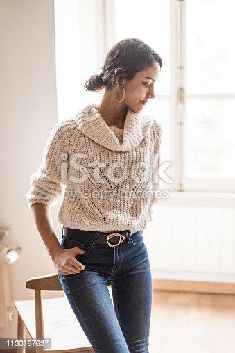 istock pensive woman posing at home 1130167637