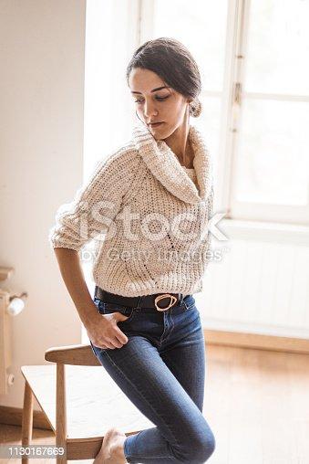 istock pensive woman posing at home 1130167669