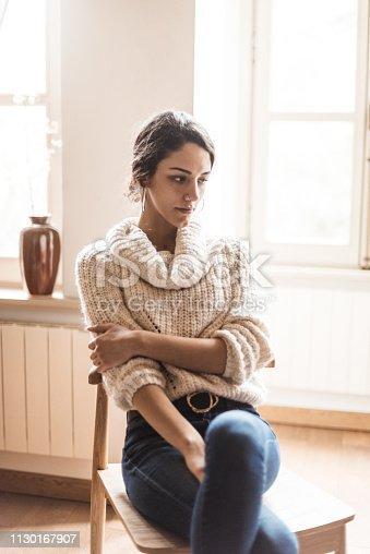 istock pensive woman posing at home 1130167907