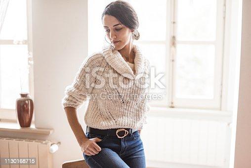 istock pensive woman posing at home 1130168715