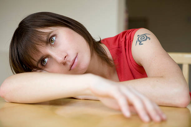 pensive woman put her head on table - deplorable stock pictures, royalty-free photos & images