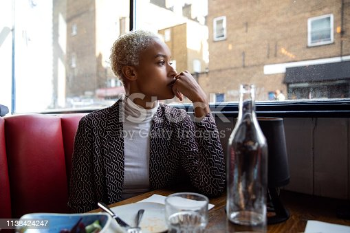 Pensive woman sitting by herself in a restaurant at lunch break