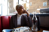 istock Pensive woman sitting by herself in a restaurant at lunch break 1138424247
