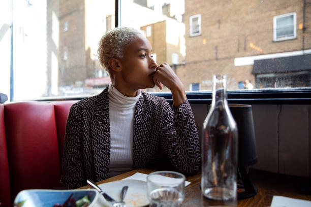 Pensive woman sitting by herself in a restaurant at lunch break Pensive woman sitting by herself in a restaurant at lunch break brood stock pictures, royalty-free photos & images