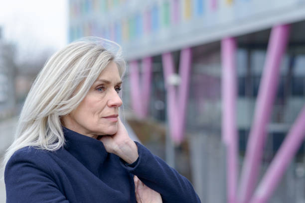 Pensive woman standing staring into the distance Pensive woman standing staring into the distance as she leans on the railing on an urban walkway resting her chin on her hands in a close up profile portrait introspection stock pictures, royalty-free photos & images