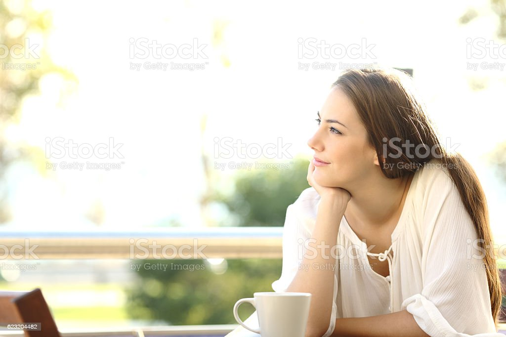 Pensive woman thinking and looking at side stock photo
