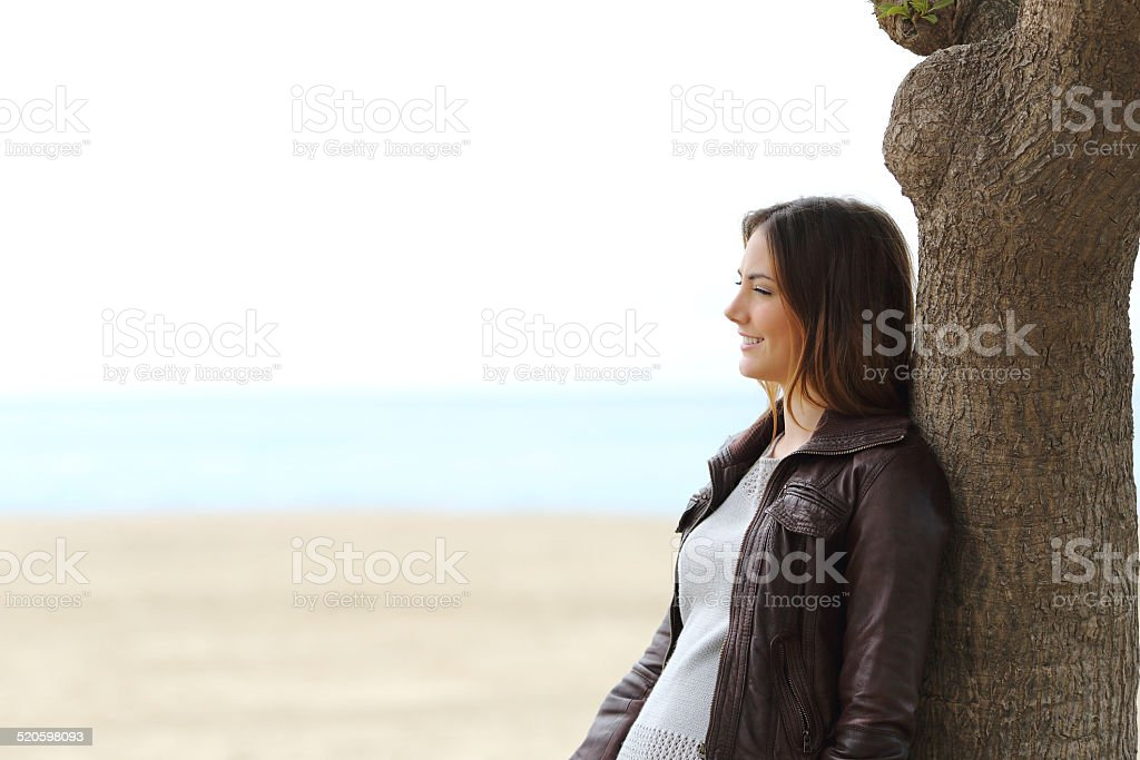 Pensive woman thinking on the beach in winter stock photo
