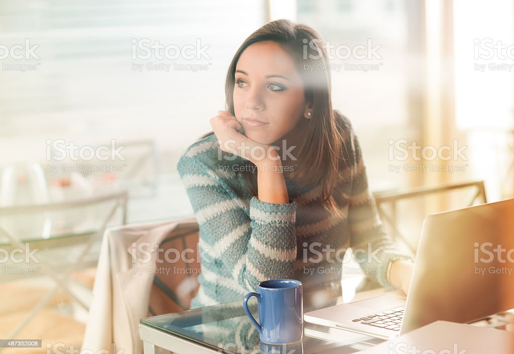 Pensive woman with laptop stock photo