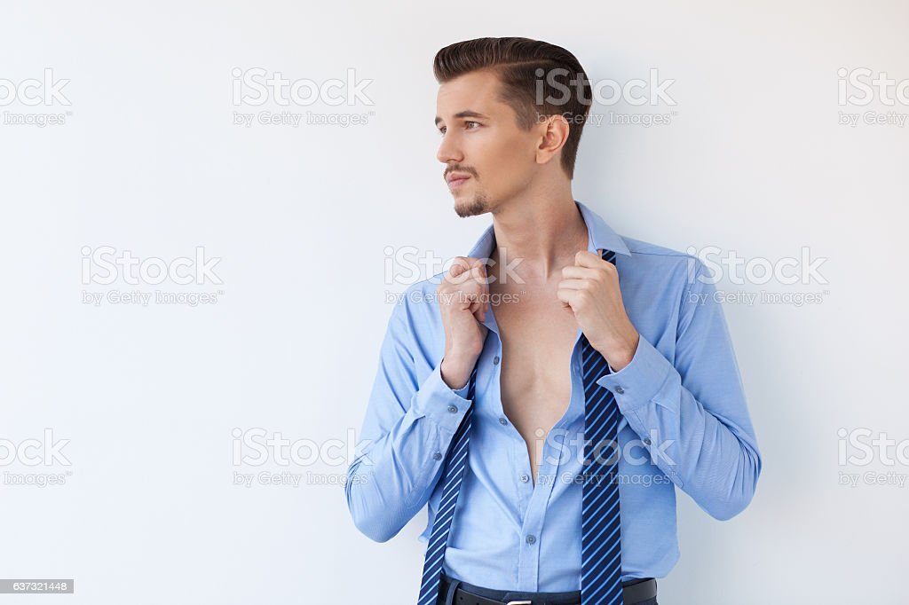 Pensive Young Attractive Business Man Undressing stock photo