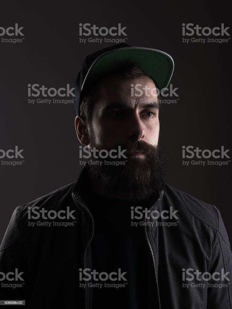 Pensive young bearded man wearing baseball cap looking away stock photo