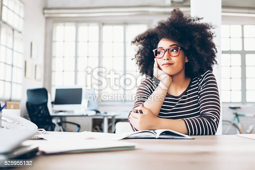 Cheerful young woman with eyeglasses sitting on desk, chin on hand, looking away. Note book, papers and tools on desk. As background tall windows, desk with computer and seat, part of a bike.