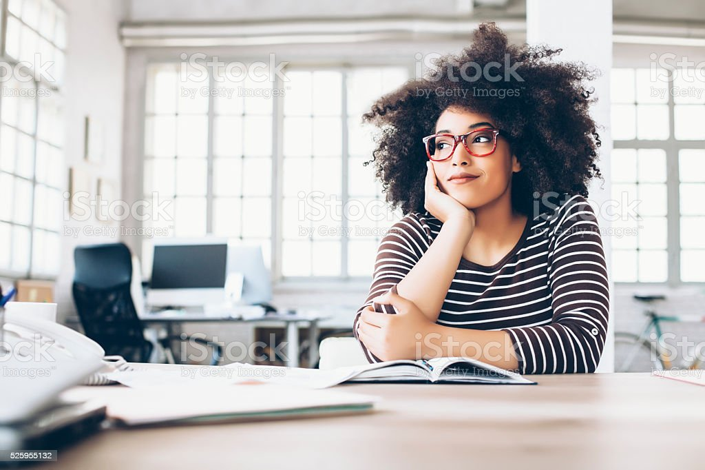 Pensive young businesswoman sitting on desk stock photo