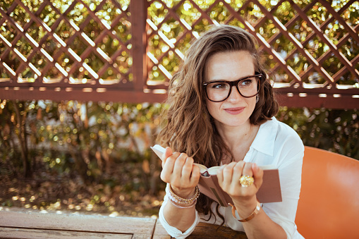 pensive young female in white shirt with book and eyeglasses