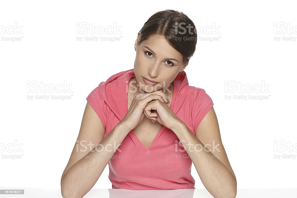 Pensive young female sitting at table stock photo