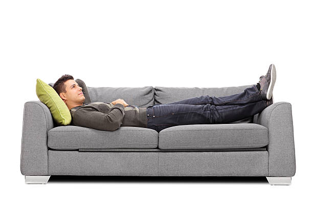 pensive young guy laying on a sofa - reclining stock photos and pictures