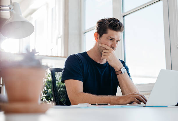 Pensive young male executive using laptop at his desk stock photo