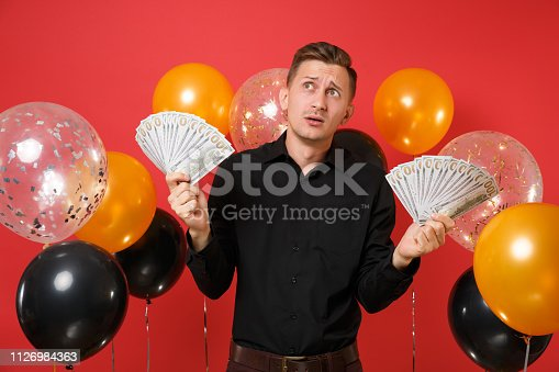 istock Pensive young man in classic shirt looking up holding bundle lots of dollars, cash money on red background air balloons. International Women's Day Happy New Year birthday mockup holiday party concept. 1126984363