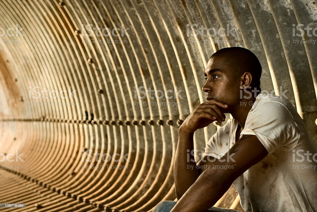 Pensive Young Man Sitting in Tunnel royalty-free stock photo
