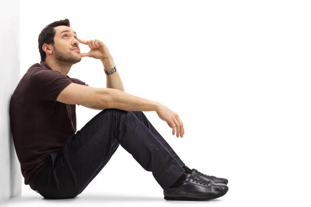 pensive young man sitting on the floor and looking up - sitting on floor stock photos and pictures