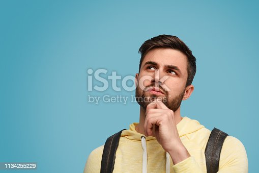 Handsome bearded guy with backpack looking up in doubts on studies against blue background