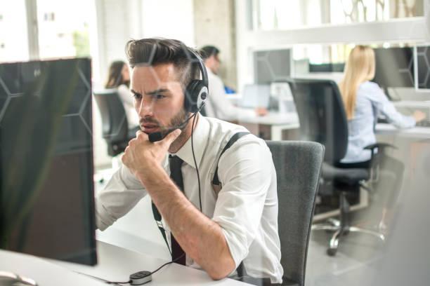 Umfassender junger Mann mit Freisprecheinrichtung mit Blick auf Computerbildschirm im Büro – Foto