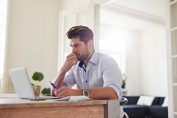 pensive young man working on laptop at home - jacob ammentorp lund stock pictures, royalty-free photos & images