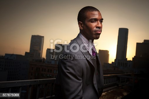 A thoughtful looking young black man stands on a balcony overlooking the financial district of Downtown Los Angeles, behind which the sun is setting.