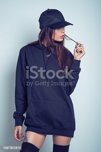 Studio portrait of beautiful young woman wearing black hooded shirt, knee socks and baseball cap, standing against grey background.