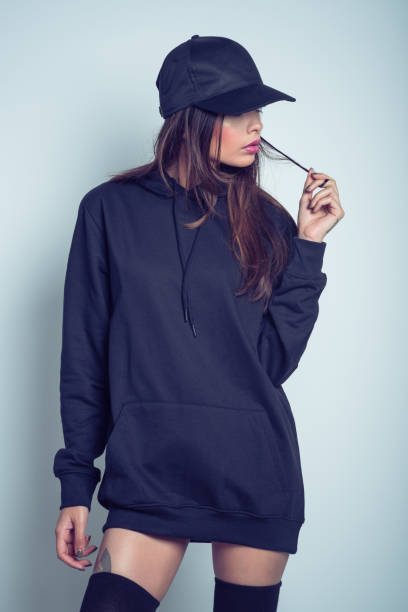 Pensive young woman in black hooded shirt and cap stock photo