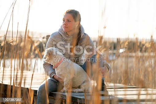 Pensive Young Woman in Jacket Sitting on Dock  Between Reed with Her Small Dog