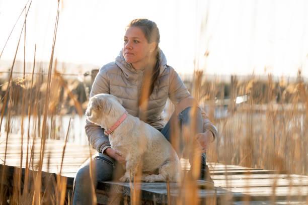 Nachdenkliche junge Frau in Jacke sitzen auf Dock zwischen Reed mit ihrem kleinen Hund - Stockfoto – Foto
