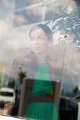istock Pensive young woman looking through a window 457790859