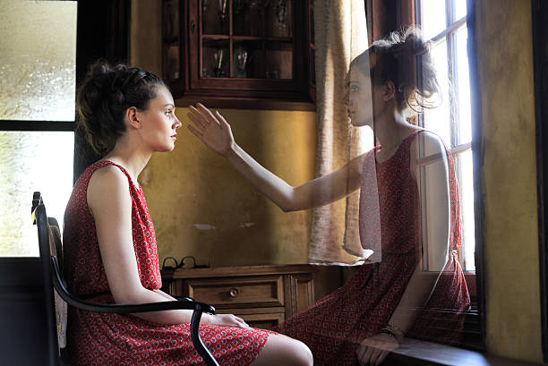 Pensive young woman looking throuth the window stock photo