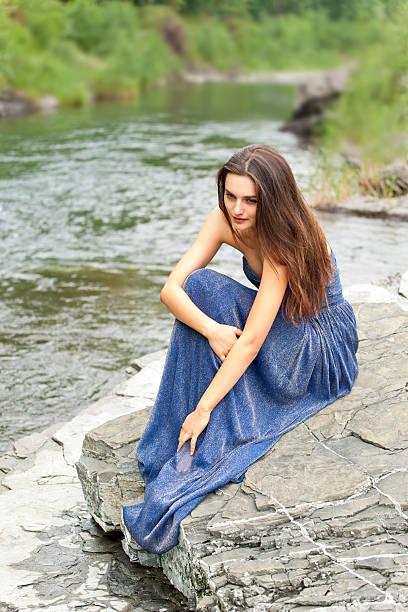 nachdenklich junge frau auf felsen am fluss - abendkleid lang blau stock-fotos und bilder